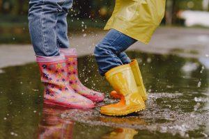 Bottes de pluie d'enfants sautant dans une flaque d'eau